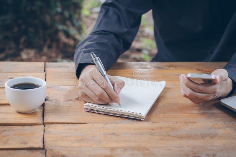 Zakończenie w górę biznesmena pisze notatniku i używać telefon komórkowy zdjęcie royalty free