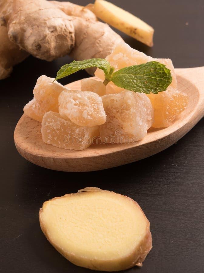 Zakończenie w górę candied krystalizujących imbirowych cukierków kawałków na drewnianej łyżce zdjęcie royalty free