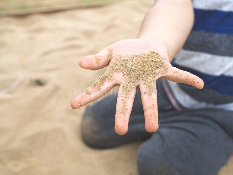 Zakończenie w górę chłopiec ręki mienia piaska na boisku fotografia stock