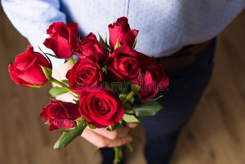 Zakończenie w górę czerwieni róży, przystojna mężczyzna walentynki dnia romantyczna niespodzianka kwitnie zdjęcia stock