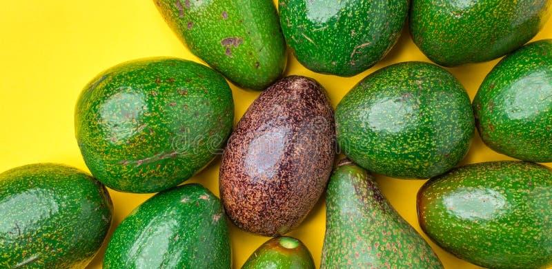 Zakończenie w górę czerwonego organicznie avocado w grupie zielonych avocados zdrowy jedzenie na koloru żółtego stołu tle nowożyt zdjęcie stock