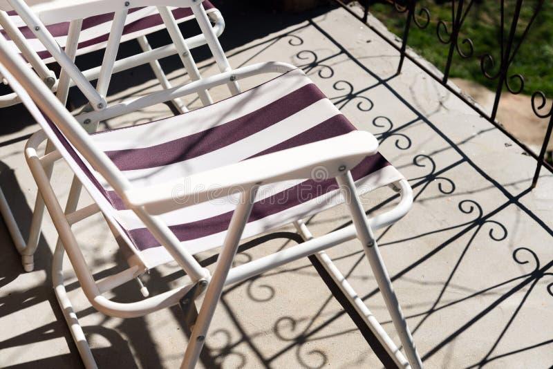 Zakończenie w górę falcowania krzesła na betonowej balkonowej podłodze z cieniami metalu balkonu ogrodzenie Relaksować na słońcu  obraz stock