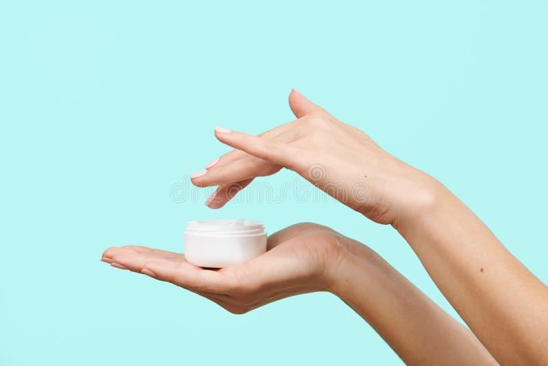Zakończenie w górę kobiet ręk trzyma moisturizer śmietankę i zamacza palec w nim, odizolowywający nad pastelowym błękitnym tłem obraz stock
