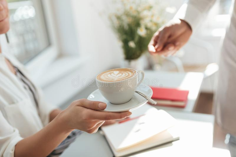 Zakończenie w górę kobiety ręki bierze filiżankę od mężczyzna ręki w sklepie z kawą zdjęcie royalty free