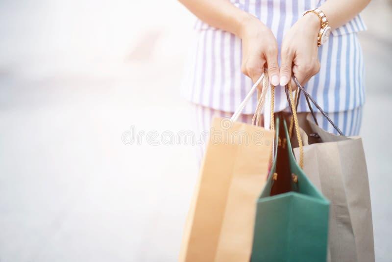 Zakończenie w górę konsumeryzm młodej kobiety mienia ręki wiele torba na zakupy w moda butiku po tym jak kupujący teraźniejszość  obrazy stock