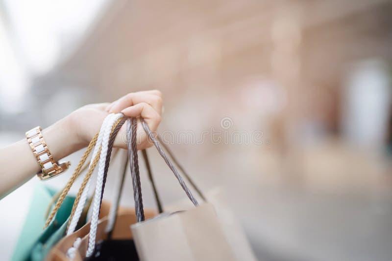 Zakończenie w górę konsumeryzm młodej kobiety mienia ręki wiele torba na zakupy w moda butiku po tym jak kupujący teraźniejszość  zdjęcia stock