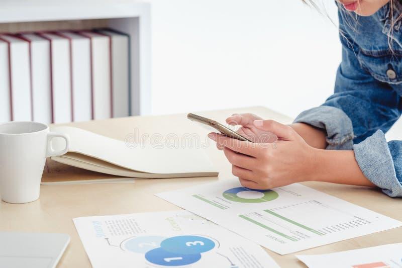 Zakończenie w górę kreatywnie dyrektora używa telefon komórkowego przy desktop stołem przy biurem pracuje z datasheet gdy planist obraz royalty free