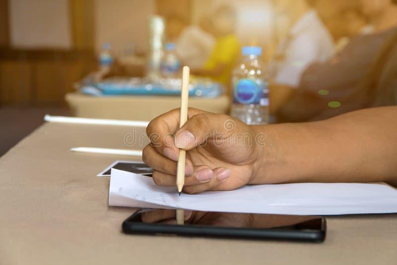zakończenie w górę mężczyzna ręki używać ołówek dla pisać na prześcieradle między spotkaniem w pokoju zdjęcie stock