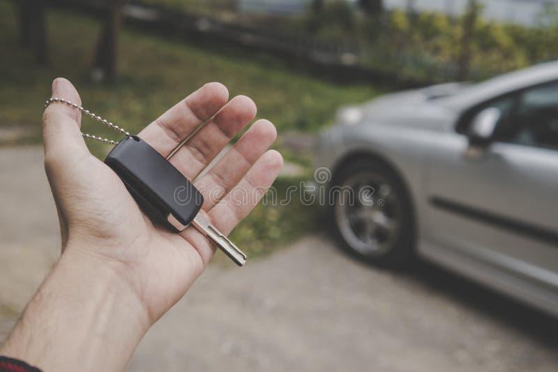Zakończenie w górę mężczyzny mienia samochodu palmowego klucza na parkującym samochodowym tle Kierowca trzyma przejazdowego klucz fotografia royalty free