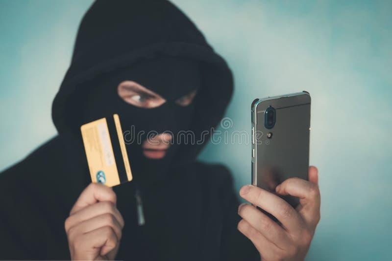 Zakończenie w górę mężczyzny w rabunek masce i kapiszonu trzyma kartę kredytową i patrzeje smartphone ekran Męska przestępca ukła zdjęcia stock