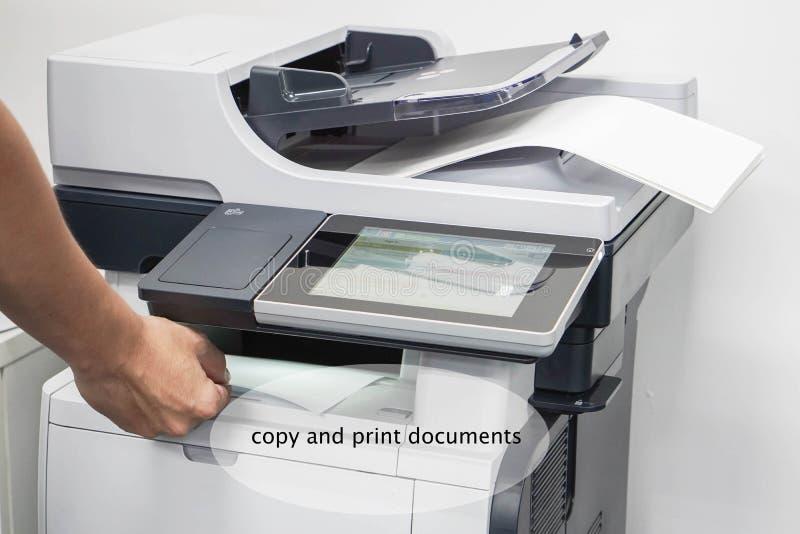 Zakończenie w górę mężczyzny wp8lywy drukujących i kopiujących biznesowych dokumentów od drukarki fotografia royalty free