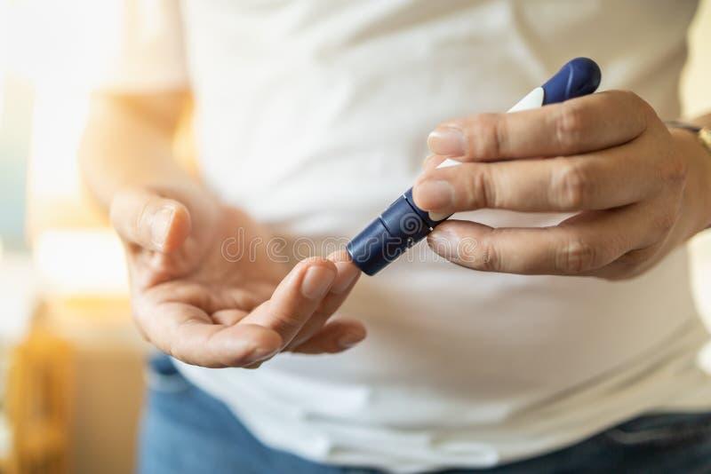 Zakończenie w górę mężczyzny wręcza używać lancet na palcu czeka krwionośnego cukieru poziom glikoza metrem Używa jako medycyna,  fotografia royalty free