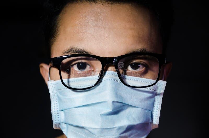 Zakończenie w górę młodego azjatykciego mężczyzny jest ubranym higieniczną maskę i szkła zdjęcie royalty free