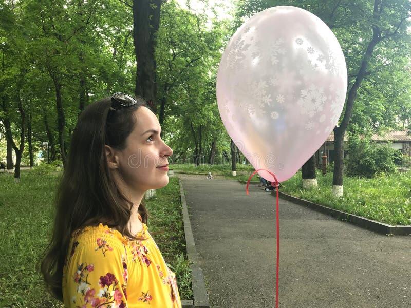 Zakończenie w górę młodej brunetki kobiety z menchia balonem w ona ręki Boczny widok obraz royalty free