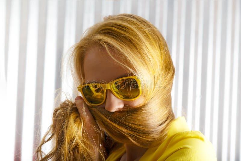 Zakończenie w górę młodej kobiety w okularach przeciwsłonecznych bawić się sztuczki z jej włosy fotografia royalty free