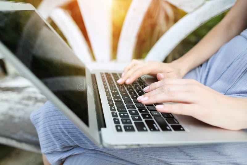 Zakończenie w górę młodych kobiet ręk palców laptopu prasowej klawiatury dla dalekiej pracy na słonecznym dniu, tło światło słone zdjęcia royalty free