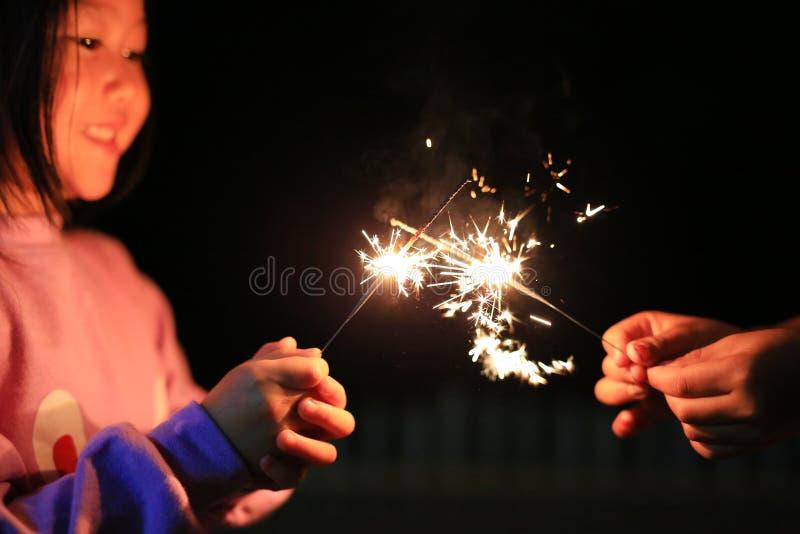 Zakończenie w górę małej Azjatyckiej dziewczyny bawić się pożarniczych sparklers w zmroku przy nocą zdjęcia stock