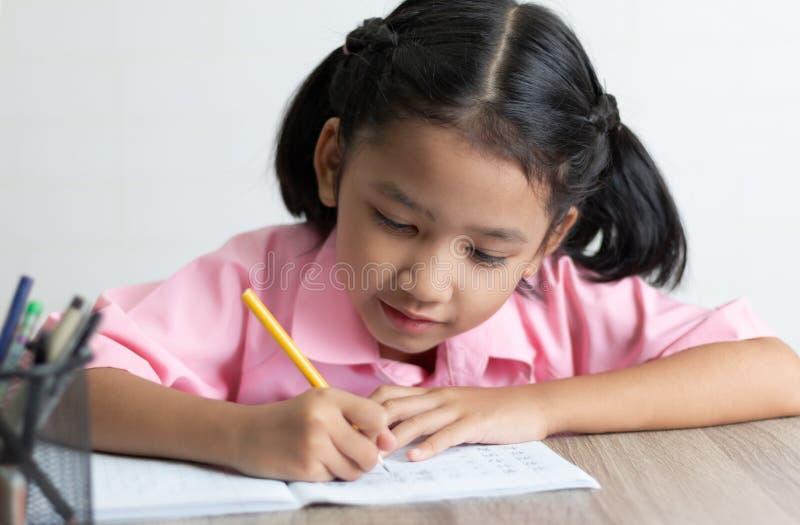 Zakończenie w górę małej dziewczynki robi pracie domowej szczęśliwie fotografia stock