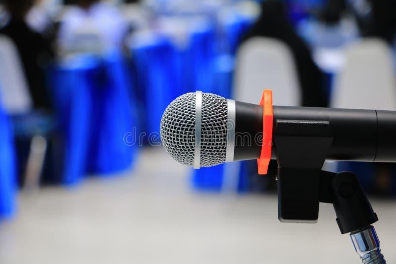 Zakończenie w górę mikrofonu bezprzewodowy starego na stole w konferenci i tło plamy wewnętrznym seminaryjnym pokoju konferencyjn obraz royalty free