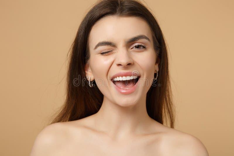Zakończenie w górę mrugać uśmiechniętej brunetki przyrodniej nagiej kobiety 20s z doskonalić skórą odizolowywającą na beżowym pas obrazy stock