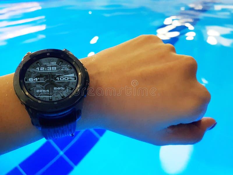 Zakończenie w górę nowożytnego mądrze zegarka przy woman's ręką w basenie obrazy stock