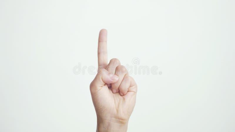 Zakończenie w górę odosobnionej żeńskiej ręki pokazuje palec wskazującego w górę odosobnionego na białym tle fotografia royalty free