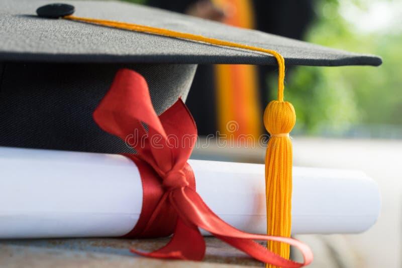 Zakończenie w górę ostrości uniwersyteta absolwenta chwytów stopnia świadectwo i skalowanie nakrętka świętuje w skalowanie ceremo zdjęcia royalty free