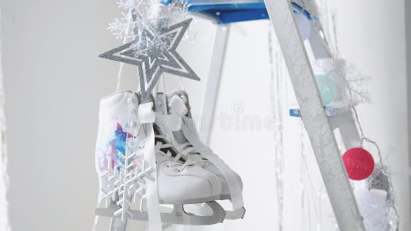 Zakończenie w górę pary białe postaci łyżwy wiesza na dekorującym stepladder Bożenarodzeniowy pojęcie fotografia royalty free