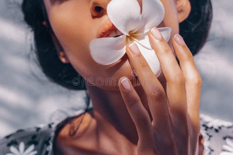 Zakończenie w górę pięknego młodej kobiety mienia frangipani kwiatu w usta fotografia royalty free