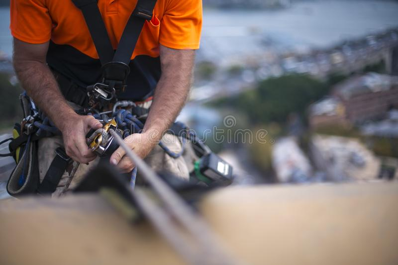 Zakończenie w górę pic męskiego arkana dostępu akcydensowy przemysłowy pracownik, używać zbawczego przyrządu descender na statycz obraz stock