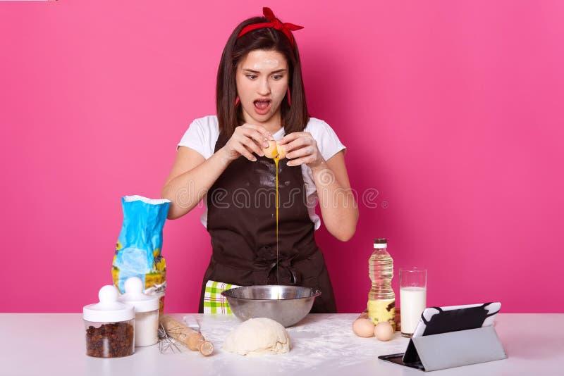 Zakończenie w górę portreta kobieta roztrzaskuje jajko dla tortowego przygotowania i uderza pięścią Pojęcie pieczenie i na obrazy royalty free