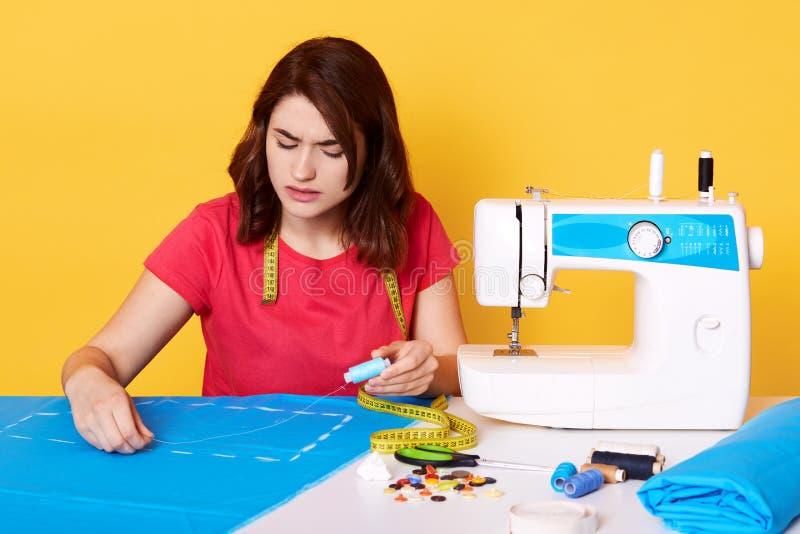 Zakończenie w górę portreta młoda brunetki szwaczka pracuje z jej wzorem na tworzeniu, trzymający niciany w rękach, koncent fotografia stock