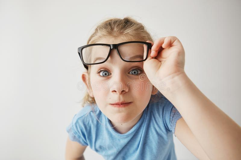 Zakończenie w górę portreta rozochocona mała dziewczyna z blondynka włosy śmiesznymi niebieskimi oczami i imituje dorosłej osoby  zdjęcia stock