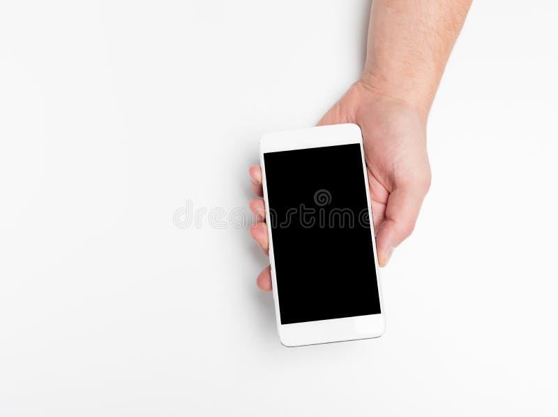 Zakończenie w górę ręka chwyta telefonu na bielu, w górę smartphone białego koloru pustego ekranu zdjęcia stock