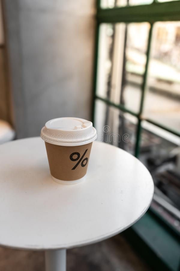 Zakończenie w górę składu papierowa gorąca filiżanka na białego metalu stole ustawia blisko szklanego okno w naturalne światło sc zdjęcie stock
