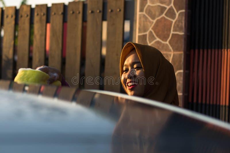 Zakończenie w górę strzału hijab kobiety samochodu płuczkowego dachu z uśmiechem obrazy stock
