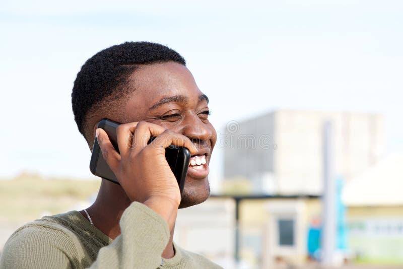 Zakończenie w górę szczęśliwego amerykanin afrykańskiego pochodzenia mężczyzny opowiada na mądrze telefonie outdoors obraz stock
