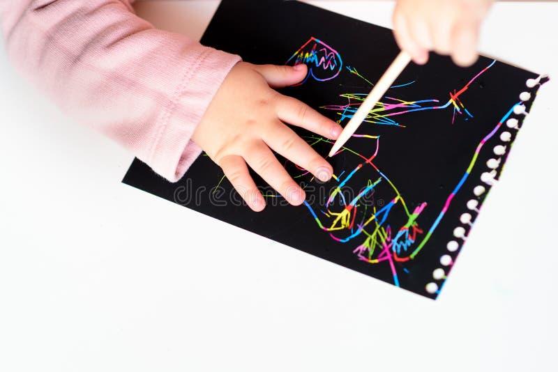Zakończenie w górę Szczęśliwych dziewczyn ręk rysuje na magicznego narysu obrazu kolorowym papierze z rysunku kijem fotografia stock