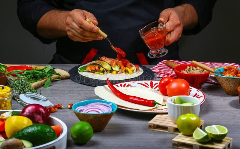 Zakończenie w górę szefa kuchni wręcza narządzanie meksykanina burito Kucbarskiego narządzania wyśmienicie meksykański burito prz fotografia stock