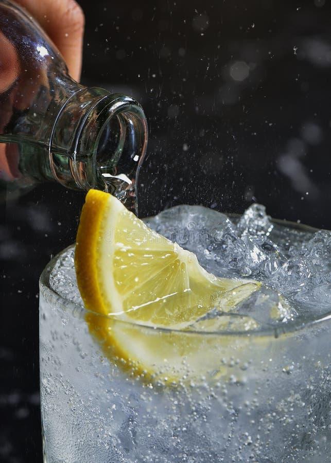 Zakończenie w górę szklanego zawiera błyska jasnego ciecza, kostka lodu i cytryna plasterka obraz stock