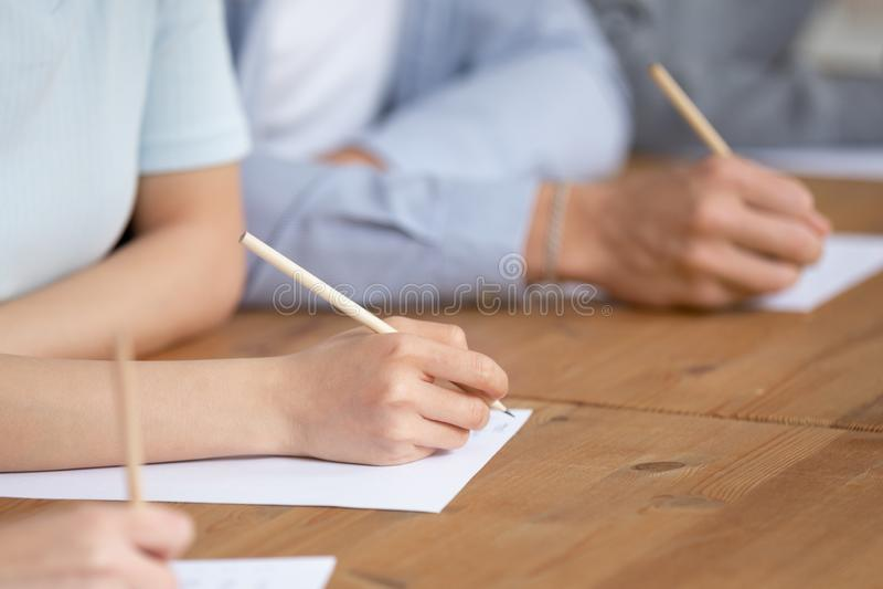Zakończenie w górę uczni pisze przelotnym tescie w sali lekcyjnej zdjęcie stock