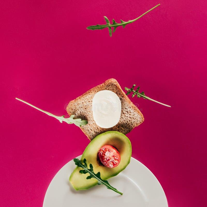 zakończenie w górę widoku grzanka kawałki avocado czereśniowego pomidoru mozzarelli ser i arugula spada na talerzu zdjęcie stock