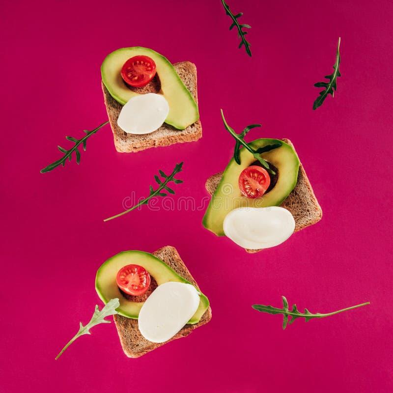 zakończenie w górę widoku levitating wznosi toast kawałki avocado czereśniowych pomidorów mozzarelli arugula i ser obraz stock