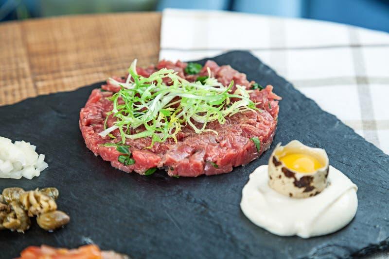 Zakończenie w górę widoku na świeży stek wołowiny tartare słuzyć na zmroku kamienia talerzu z kumberlandem i surowym przepiórki j obraz royalty free