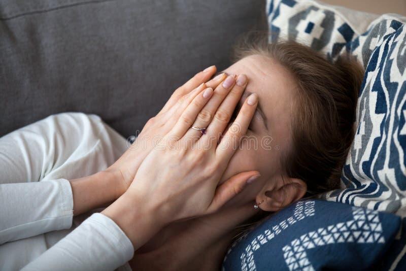 Zakończenie w górę wzburzonej sfrustowanej kobiety nakrycia twarzy z rękami, kłama na kanapie fotografia stock