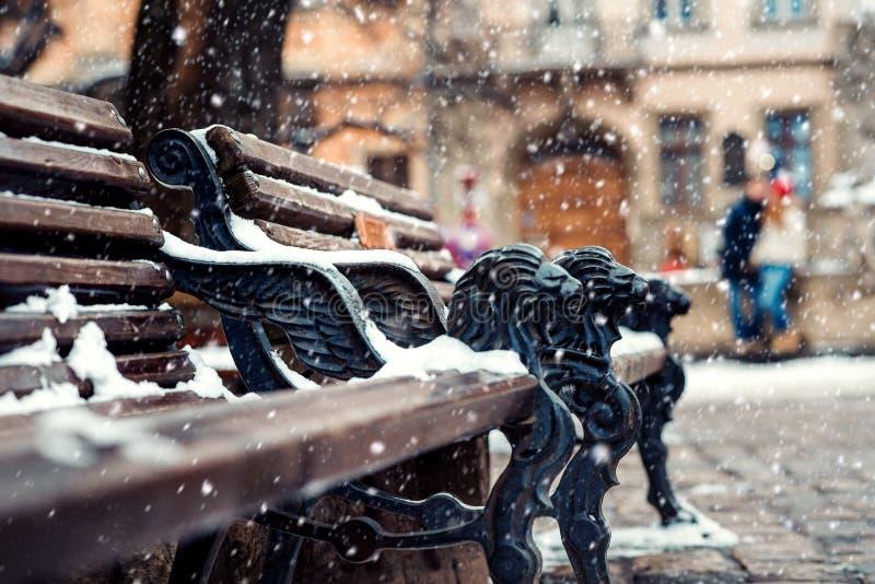Zakończenie widok ławka z żelaznymi lew dekoracjami zakrywać z puszystym śniegiem Przytulenie para z psem przy zdjęcie stock
