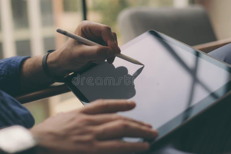Zakończenie widok biznesmen używa stylus pióro dla pracować na cyfrowym pastylka ekranie przy biurem zamazujący tło obraz stock