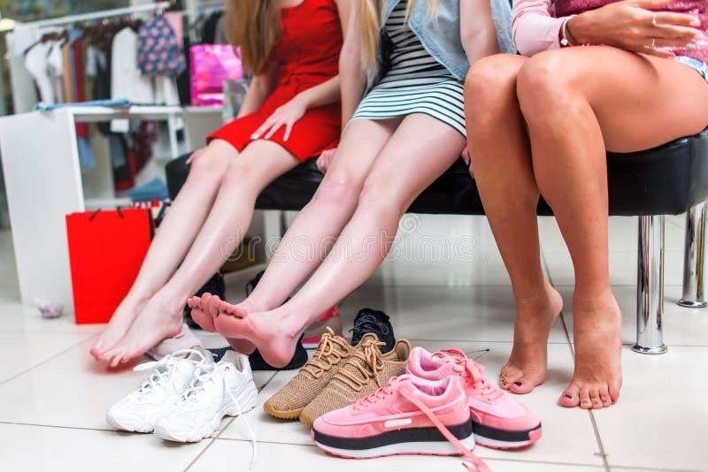 Zakończenie widok bose długie szczupłe kobiet nogi otaczać rozmaitością sportów buty Trzy przyjaciół żeński siedzieć obraz stock