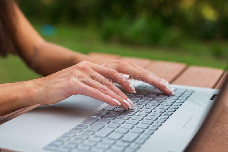 Zakończenie widok kobiet ręki na laptop klawiaturze Studencki uczyć się outdoors zdjęcia royalty free