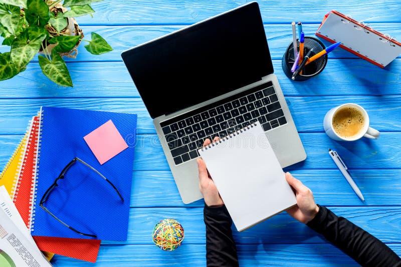 Zakończenie widok notepads w rękach laptopem na błękicie obraz royalty free
